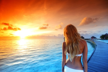 woman in a dress on a bridge home sea and the maldivian sunset on the background photo