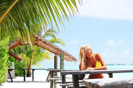 woman sitting in a tropical cafe on the background of a  palm trees and sky and sea photo
