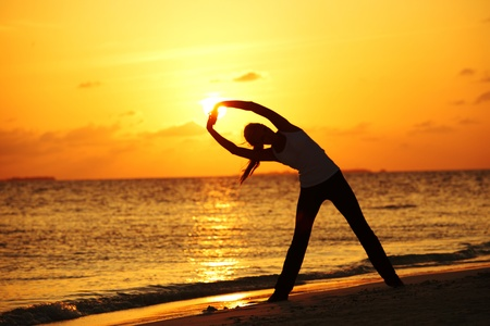 sunset yoga woman on sea coast Stock Photo