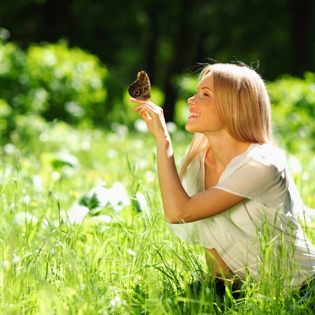 Woman playing with a butterfly on green grass Stock Photo - 12451856