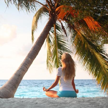 yoga woman on sea coast under palm