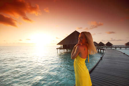 wet dress: woman in a dress on a bridge home sea and the maldivian sunset on the background