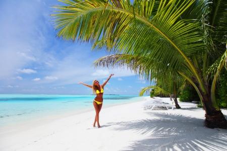 woman in bikini under palm on sea background photo