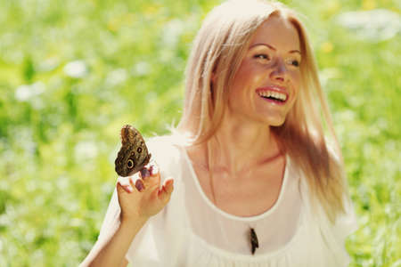 Woman playing with a butterfly on green grass Stock Photo - 12451720