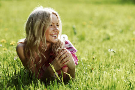 girl with a dandelion in his hand lying on the grass photo
