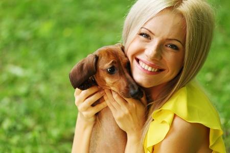 mujer con perro: Dachshund mujer en sus brazos en la hierba Foto de archivo