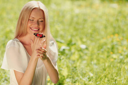 Woman playing with a butterfly on green grass Stock Photo - 12613457