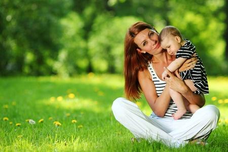 familia en jardin: Feliz madre e hija en la hierba verde