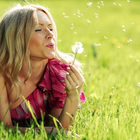 viento soplando: chica con un diente de le�n en la mano tendida en la hierba Foto de archivo