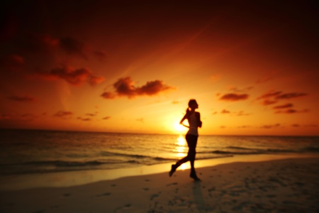 woman run along the sea coast of sunrise behind Stock Photo - 13044875
