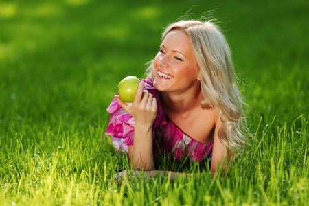 blonde holding an apple in his hand lying on green grass photo