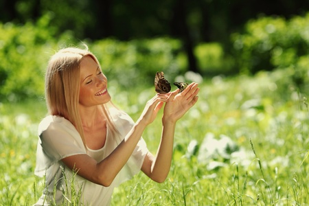 Woman playing with a butterfly on green grass Stock Photo - 13063039