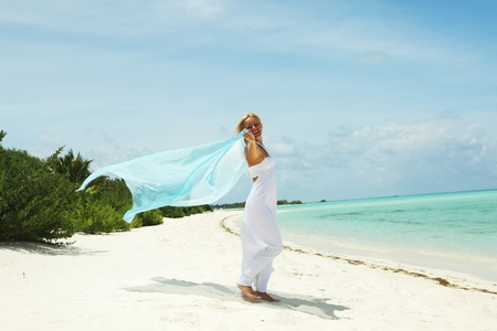 breeze: woman with a white fabric in his hands on the beach