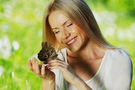 Woman playing with a butterfly on green grass Stock Photo - 13168946