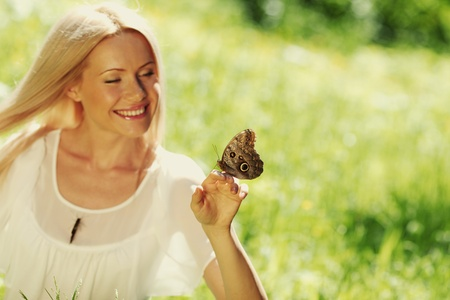 Woman playing with a butterfly on green grass Stock Photo - 13168943