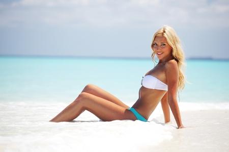 piernas sexys: mujer acostada en la arena de la costa del océano Foto de archivo