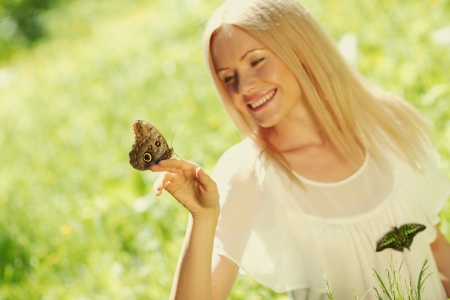 Woman playing with a butterfly on green grass photo