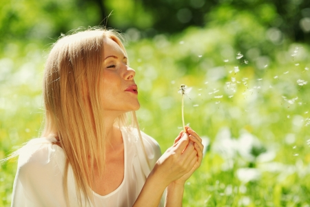 girl blowing: girl blowing on a dandelion lying on the grass