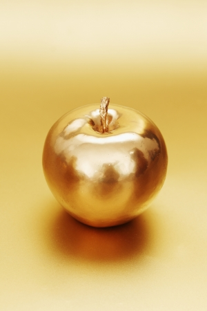 gold apple on gold background Stock Photo - 13628744