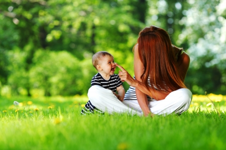 Heureuse m�re et fille sur l'herbe verte photo