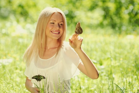 Woman playing with a butterfly on green grass Stock Photo - 13629245