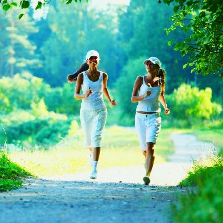 ジョグ: 日当たりの良い夏の日に緑豊かな公園で走っている美しい若い女性