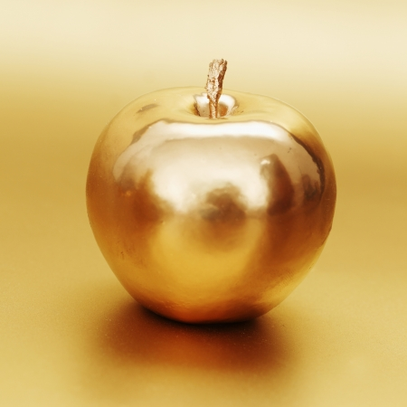 gold apple on gold background Stock Photo - 13799721