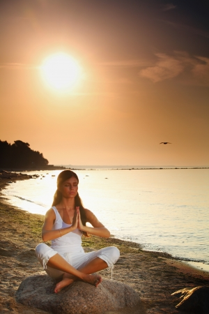 Silhouette of woman in yoga lotus meditation position front to seaside photo