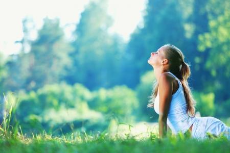 Jonge vrouw doet yoga oefening in het groen park Stockfoto - 13843150