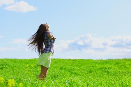 exuberance: woman on summer green field feel freedom Stock Photo
