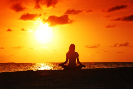 yoga meditation: sunset yoga woman on sea coast Stock Photo