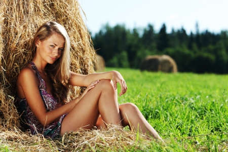 cute young farm girl: portrait of a girl next to a stack of hay under the blue sky
