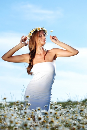 beautiful girl  in dress on the daisy flowers field  Stock Photo - 14449077