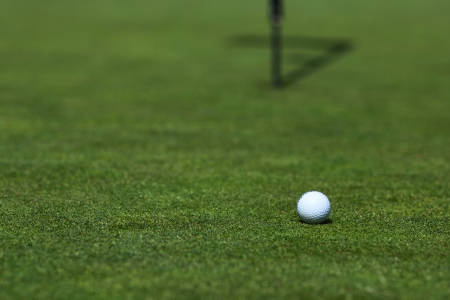 golf ball on lip of cup photo