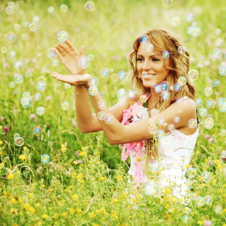 day dream:  Blonde starts soap bubbles in a green field Stock Photo