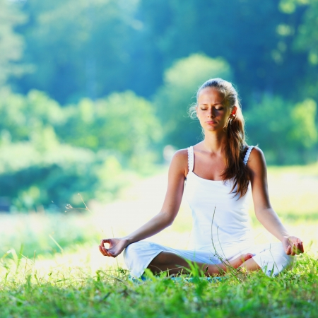 Young woman doing yoga exercise in green park photo