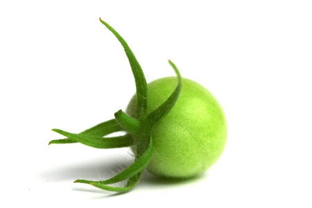 green tomato isolated on white photo