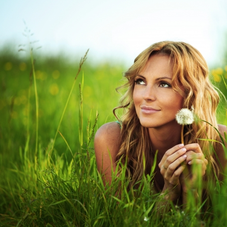 girl blow on dandelion on green field photo