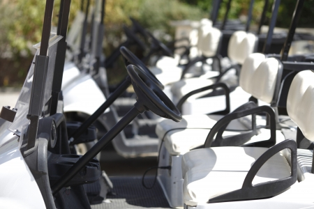 A number of the golf carts at the golf course photo