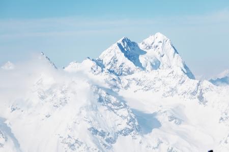 snow climbing: top of alps in sky Stock Photo