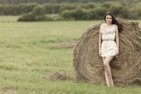 cute young farm girl: portrait of a girl next to haystack