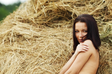 haystacks: portrait of a girl next to haystack