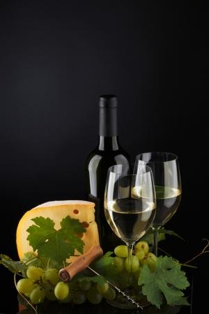 tabla de quesos: vino blanco y queso en negro Foto de archivo