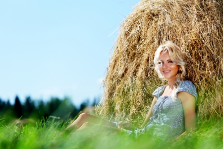 portrait of a girl next to a stack of hay under the blue sky photo