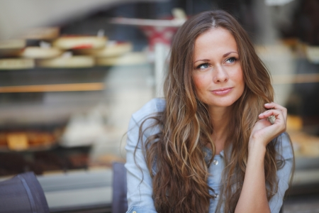 attractive gorgeous: beautiful young woman sitting alone in street cafe