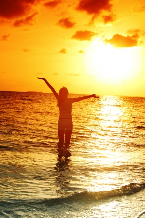 happy woman standing on a sunset in ocean waves photo