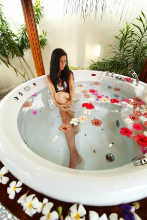 Pretty woman relaxing in a small pool with flower petals photo