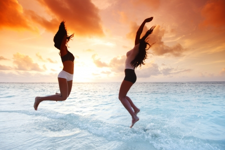 Two happy women jumping on sunset beach near sea photo
