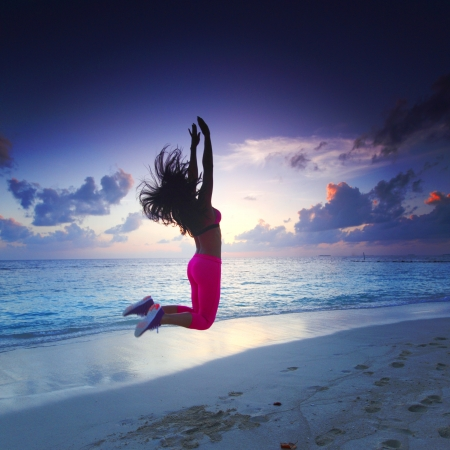 jumping: Mujer joven saltando con las manos levantadas en Sunset Beach