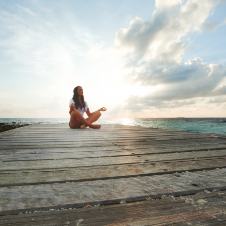 Young beautiful woman in lotus pose meditating near sea alone